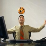 Businessman Heading Soccer Ball at Desk